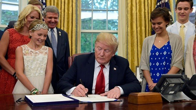 President Donald Trump signs the STAR Act during a ceremony in the Oval Office on June 5, 2018. Cancer survivor Sadie Keller, 11, and her mother Sarah Keller watch at left. (AP Photo/Susan Walsh)