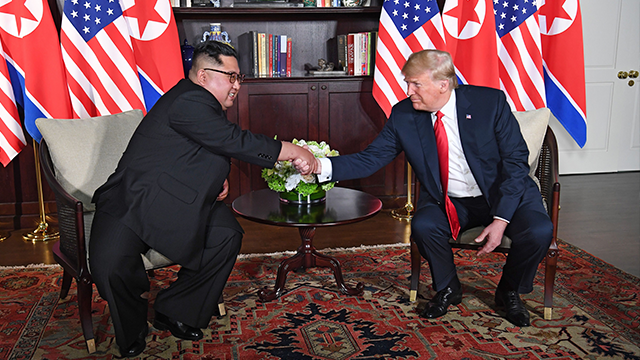 US President Donald Trump (R) shakes hands with North Korea's leader Kim Jong Un (L) as they sit down for their historic US-North Korea summit, at the Capella Hotel on Sentosa island in Singapore on June 12, 2018. (SAUL LOEB/AFP/Getty Images)