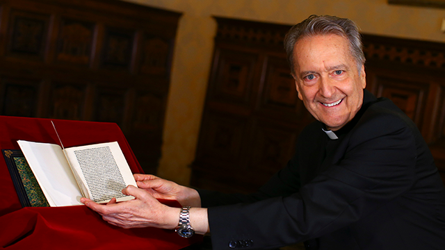 Prefect of the Vatican Library Bishop Cesare Pasini leafs through an authentic 15th Century copy of a letter written by Christopher Columbus, at the Vatican, Thursday, June 14, 2018. (Tony Gentile/Pool Photo via AP)