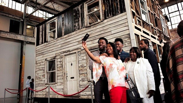 Visitors take a photo April 1, 2018, in front of the rebuilt house of Rosa Parks at the WaterFire Arts Center, in Providence. Rosa Parks moved to the house in Detroit in 1957, two years after refusing to give up her bus seat. (AP Photo/Steven Senne)