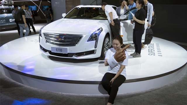 A woman poses for a photo in front of a CT6 Cadillac during the Consumer Electronics Show Asia 2018 in Shanghai, China on Friday, June 15, 2018. (AP Photo/Sam McNeil)