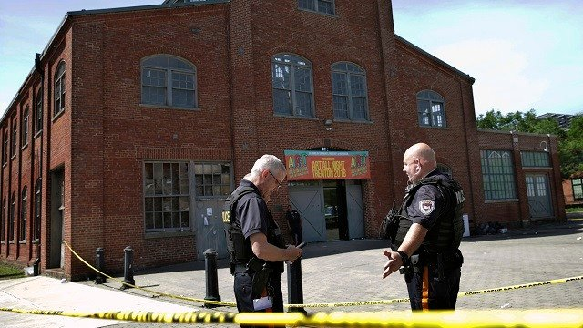 Police stand guard outside the warehouse building where the Art All Night Trenton 2018 festival that was the scene of a shooting that resulted in numerous injuries and at least one death Sunday, June 17, 2018, in Trenton, N.J. (AP Photo/Mel Evans)