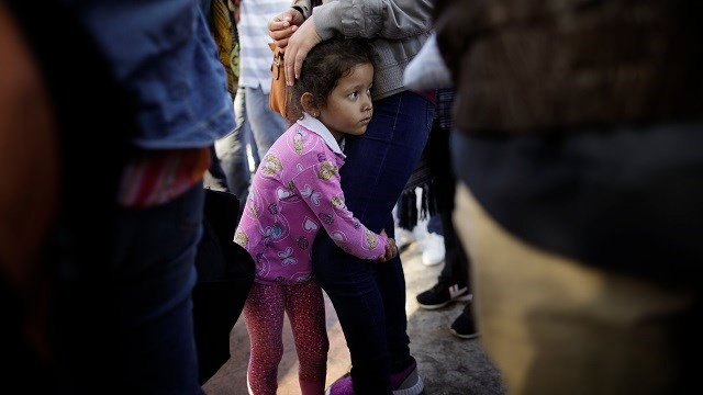 Nicole Hernandez, of Mexico, holds on to her mother as they wait with other families to request political asylum in the United States, across the border in Tijuana, Mexico on June 13, 2018. (AP Photo/Gregory Bull)