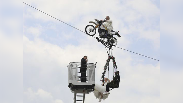 Pastor Stefan Gierung, left, stands in a cage atop of a fire service ladder in front of bride Nicole Backhaus, center, and groom Jens Knorr, right, both sitting in a swing dangling under a motorcycle with artist Falko Traber, top. (Peter Gercke, AP)