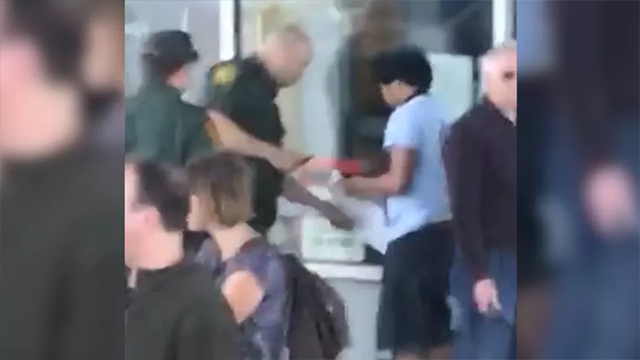 This image from a cellphone video shows a CBP officer screening a passenger in Bangor. (CNN)