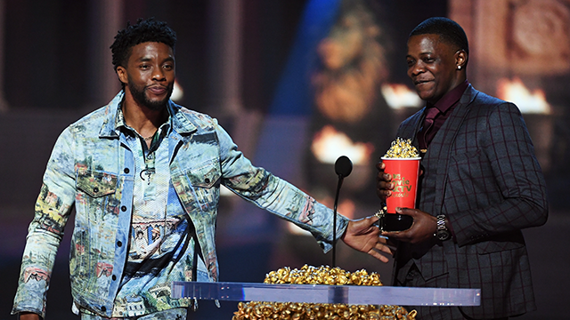 Actor Chadwick Boseman (L), winner of the Best Hero award for 'Black Panther,' presents his trophy to James Shaw Jr. onstage during the 2018 MTV Movie And TV Awards. (Photo by Kevin Winter/Getty Images)