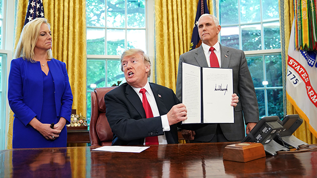 Watched by Homeland Security Secretary Kirstjen Nielsen (L) and Vice President Mike Pence, US President Donald Trump holds an executive order on immigration which he just signed in the Oval Office of the White House on June 20, 2018 (MANDEL NGAN/Getty)