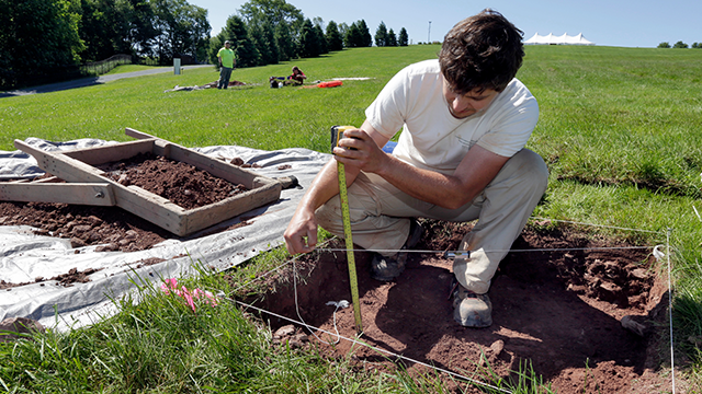 In this Thursday, June 14, 2018 photo, Paul Brown, of the Public Archaeology Facility at Binghamton University, measures a dig at the site of the original Woodstock Music and Art Fair, in Bethel, N.Y. (AP Photo/Richard Drew)