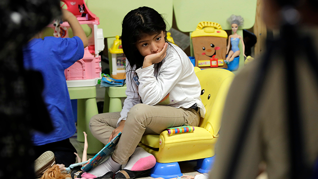 An immigrant child from Guatemala sits on a toy chair as she waits with her family at the Catholic Charities RGV, Thursday, June 21, 2018, in McAllen, Texas. (AP Photo/David J. Phillip)