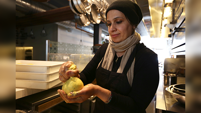 In this photo taken June 20, 2018, Muna Anaee, prepares a ball of khobz orouk, a flatbread she would eat frequently in her native Iraq, at the Tawla restaurant kitchen in San Francisco during the inaugural Refugee Food Festival. (AP Photo)