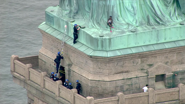 Woman climbs Base of Statue of Liberty amid Protest
