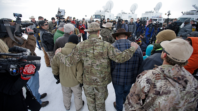 Members of the group occupying the Malheur National Wildlife Refuge headquarters hug after Ammon Bundy, center, left, one of the sons of Nevada rancher Cliven Bundy, spoke with reporters during a news conference Monday, Jan. 4, 2016, near Burns, Ore. (AP)