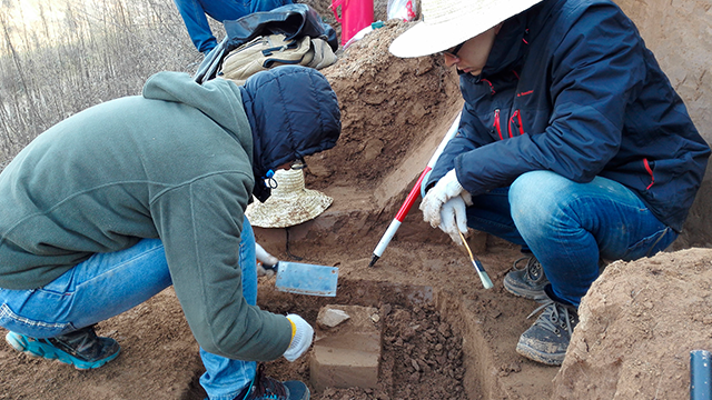 In this Sunday, Dec. 10, 2017 photo provided by Zhaoyu Zhu, scientists examine a pointed piece of quartzite rock that was unearthed from the oldest layer of dirt at a site in the Loess Plateau in China. (Zhaoyu Zhu via AP)