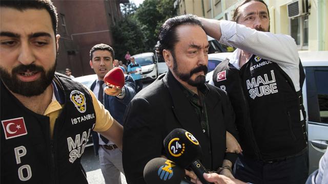 Turkish police officers escort televangelist Adnan Oktar after his arrest in Istanbul. (Getty Images via CNN)