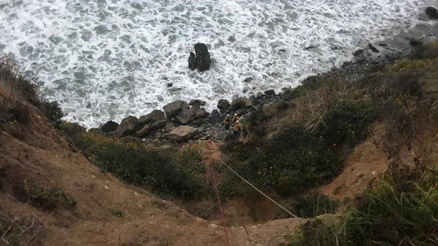 Rescuers stand at the bottom of a cliff along the California coastline where they found a missing Portland woman a week after she disappeared