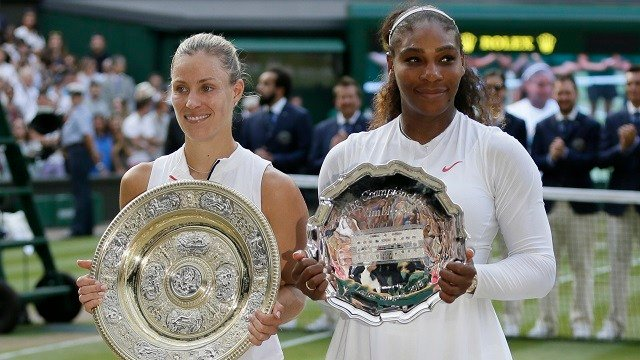 Angelique Kerber of Germany holds the winner's trophy after defeating Serena Williams of the United States, right, in the women's singles final match at the Wimbledon Tennis Championships, in London, Saturday July 14, 2018. (AP Photo/Tim Ireland)