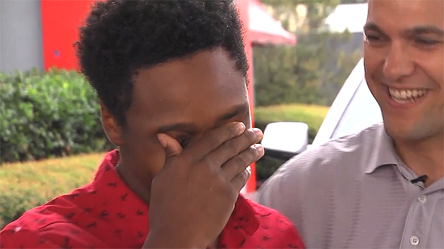 Walter Carr is tearful as he's surprised with a new car after walking 20 miles to work. (WMBA via CNN)