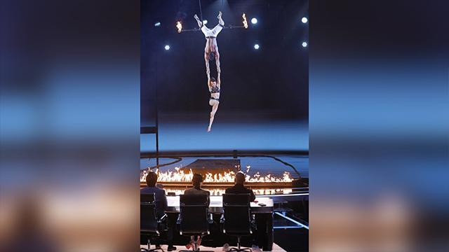 "Husband and wife trapeze performers Mary and Tyce, known as ""Duo Transcend,"" were performing their routine when she slipped through his hands and fell to the ground. (Trae Patton/NBC)"