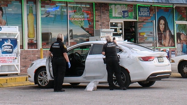 Police stand outside a convenience store where one person was killed during a dispute over a parking space. (WFTS/CNN)