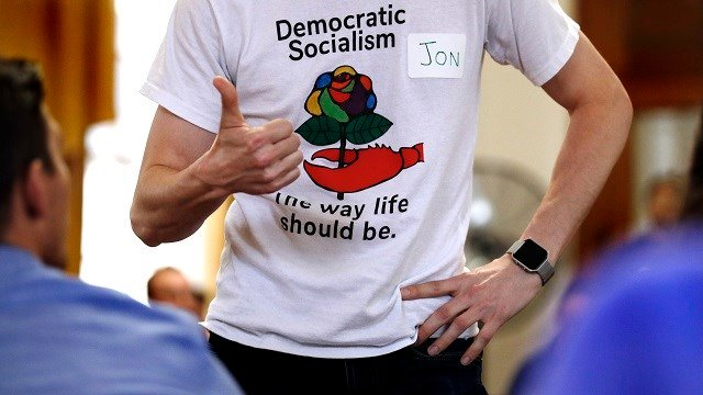 Jon Torsch wears a t-shirt promoting democratic socialism during a gathering of the Southern Maine Democratic Socialists of America at City Hall in Portland, Maine, Monday, July 16, 2018. (AP Photo/Charles Krupa)