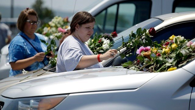 People leave flowers on cars believed to belong to victims of a duck boat accident, Friday, July 20, 2018 in Branson, Mo. Seventeen people were killed when a tourist boat capsized. (AP Photo/Charlie Riedel)