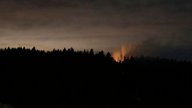 Smoke and fire are seen on Ketron Island in Washington state Aug. 11, 2018. An airline mechanic stole an empty plane, took off from Seattle-Tacoma International Airport and was chased by military jets before crashing. (AP Photo/Ted S. Warren)