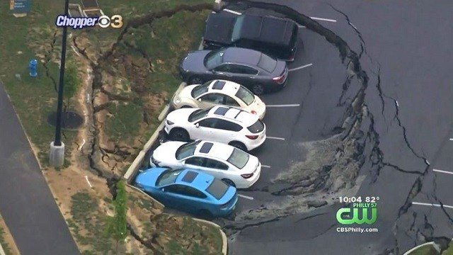 Six cars fell into a sinkhole at an outlet mall parking lot in Pennsylvania. (KYW via CNN Wire)
