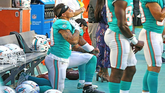 Miami Dolphins receivers Kenny Stills and Albert Wilson kneel during the national anthem as they prepare to play the Tampa Bay Buccaneers at Hard Rock Stadium in Miami Gardens, Fla., on Thursday, Aug. 9, 2018. (Charles Trainor Jr./Miami Herald/ via Getty)
