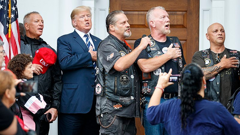 President Donald Trump stands in the rain with members of Bikers for Trump and supporters as they say the Pledge of Allegiance, Saturday, Aug. 11, 2018, at the clubhouse of Trump National Golf Club in Bedminster, N.J. (AP Photo/Carolyn Kaster)