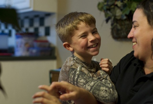 Joel Evans, 7, and his mom Sabrina Evans laugh at their home. (David S. Holloway/CNN)