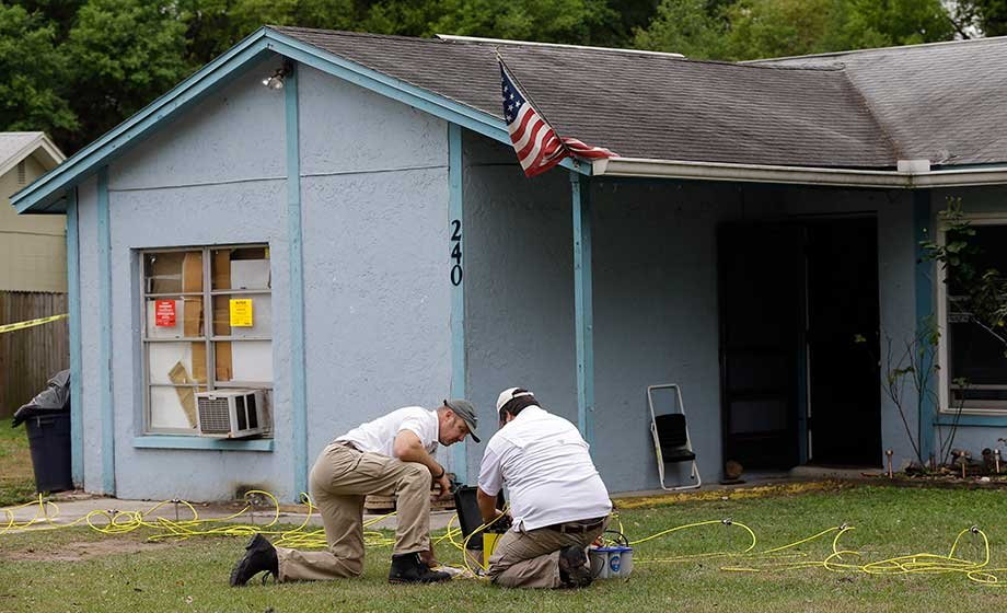 Engineers work in front of a home where sinkhole opened up underneath a bedroom and swallowed a man Friday, March 1, 2013, in Seffner, Fla. (Source: AP Photo)