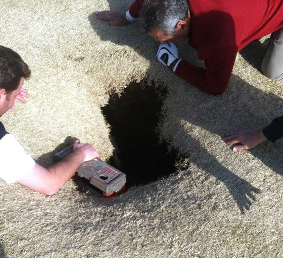 This March 8, 2013 photo provided by Golfmanna shows golfers looking into a sinkhole that opened up under golfer Mark Mihal on the 14th hole of a golf course in Waterloo, Ill.  (AP Photo/Courtesy Golfmanna)