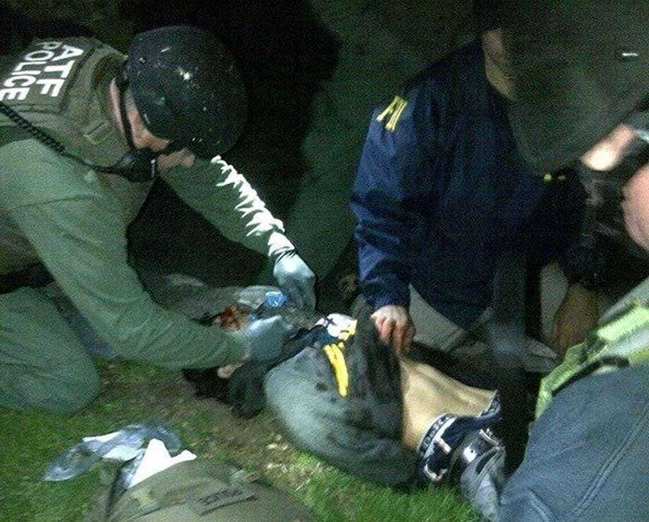 In this April 19, 2013 photo obtained by The AP, ATF and FBI agents check suspect Dzhokhar Tsarnaev for explosives and also give him medical attention after he was apprehended in Watertown, Mass.