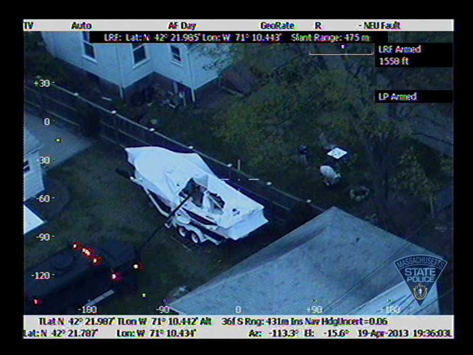 Authorities use heavy artillery vehicle to remove boat tarp where suspect was hiding out. (Massachusetts State Police)