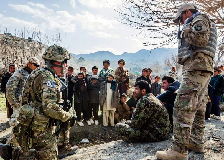 Afghan children gather to watch as U.S. Army Capt. Andrew Jenkins, left kneeling, meets with his counterpart from the Afghan army in a remote village of Khowst province, Afghanistan in 2013.