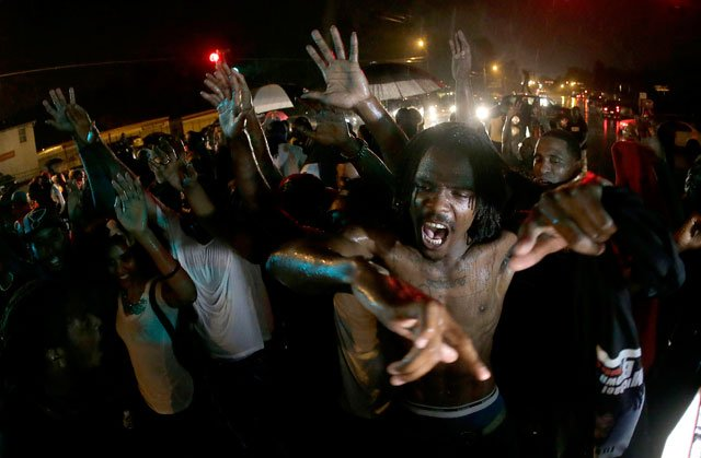 People defy a curfew Sunday, Aug. 17, 2014, before smoke and tear gas was fired to disperse a crowd protesting the shooting of teenager Michael Brown last Saturday in Ferguson, Mo. (AP Photo/Charlie Riedel)