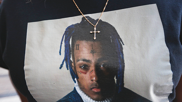 A fan wears a cross around her neck dangling on a t-shirt in remembrance before she enters a memorial for the rapper, XXXTentacion, Wednesday, June 27, 2018, in Sunrise, Fla. (AP Photo/Brynn Anderson)