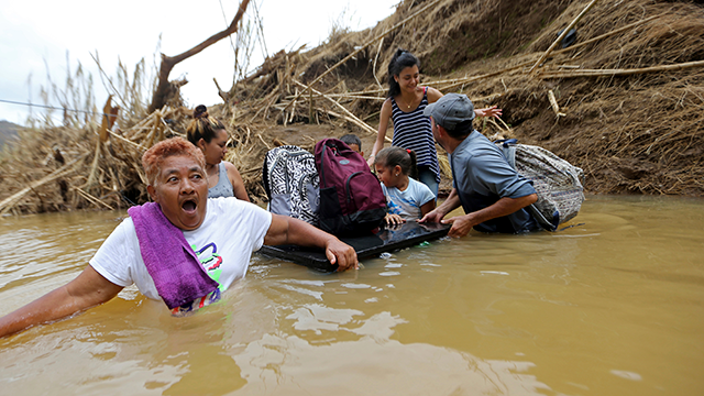 Marta Sostre Vazquez reacts as she starts to wade into the San Lorenzo Morovis river with her family, after the bridge was swept away by Hurricane Maria, in Morovis, Puerto Rico, Wednesday, Sept. 27, 2017. (AP Photo/Gerald Herbert)
