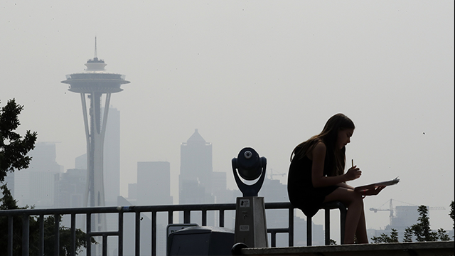 Smoky haze obscures the Space Needle and downtown Seattle on Aug. 14. (Elaine Thompson/AP)