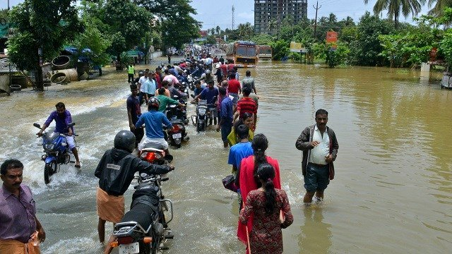 People move past a flooded road in the southern Indian state of Kerala on Aug. 17, 2018. Rescuers evacuated thousands of people stranded on their rooftops following unprecedented flooding that killed more than 320 people. (AP Photo)