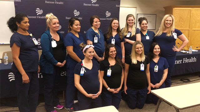 Twelve of the 16 pregnant nurses at Banner Desert Medical Center in Mesa, Arizona, pose for a photo. (Banner Desert Medical Center via CNN)